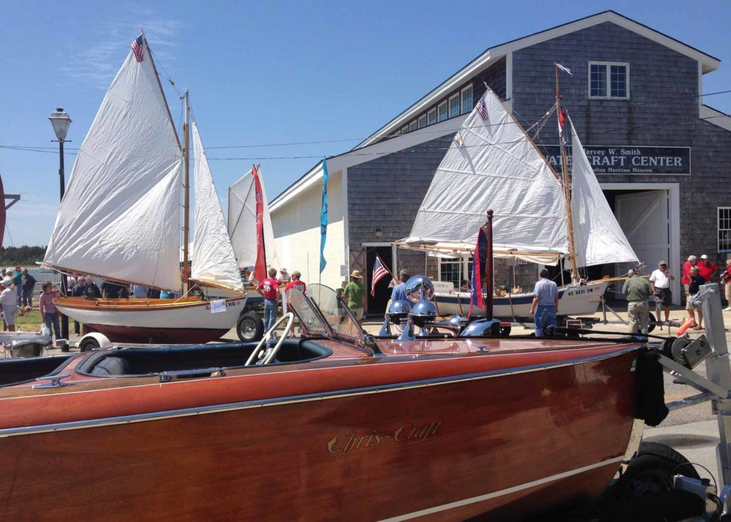 People gathered touring a display of wooden boats