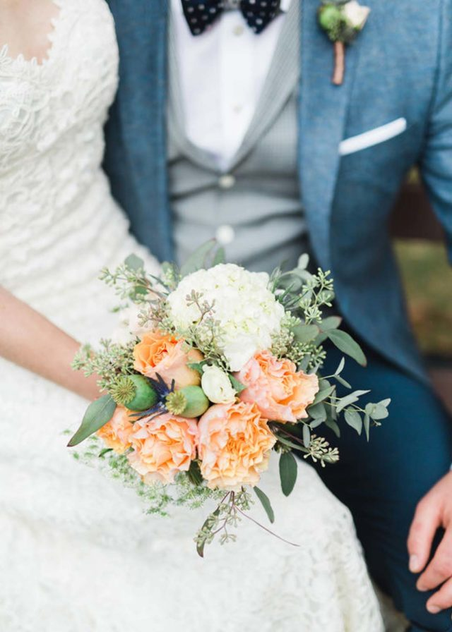 bride and groom sitting beside one another, bride holding blush flower bouquet