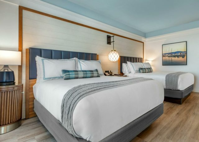 Double Queen Room with wooden accent wall, decorative lights and fresh bedding