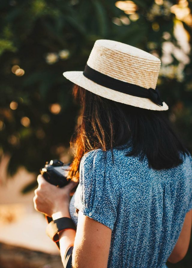 woman wearing a blue dress and straw hat browsing her recent photos on dslr camera