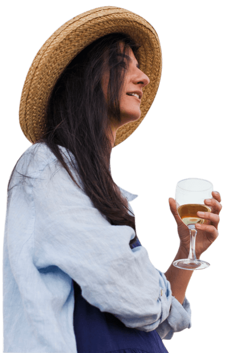 woman in straw hat smiling holding a glass of white wine