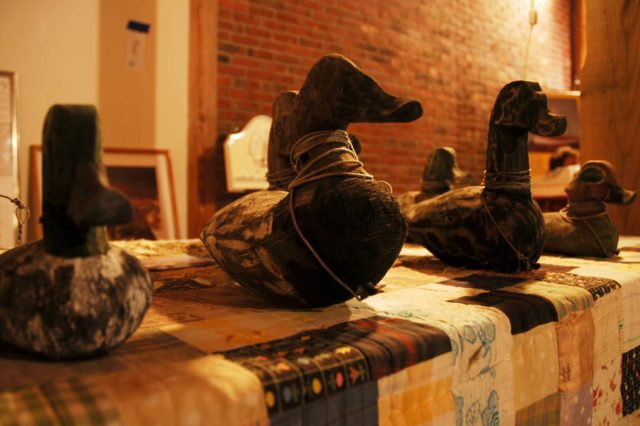 three wooden ducks in a row in a museum