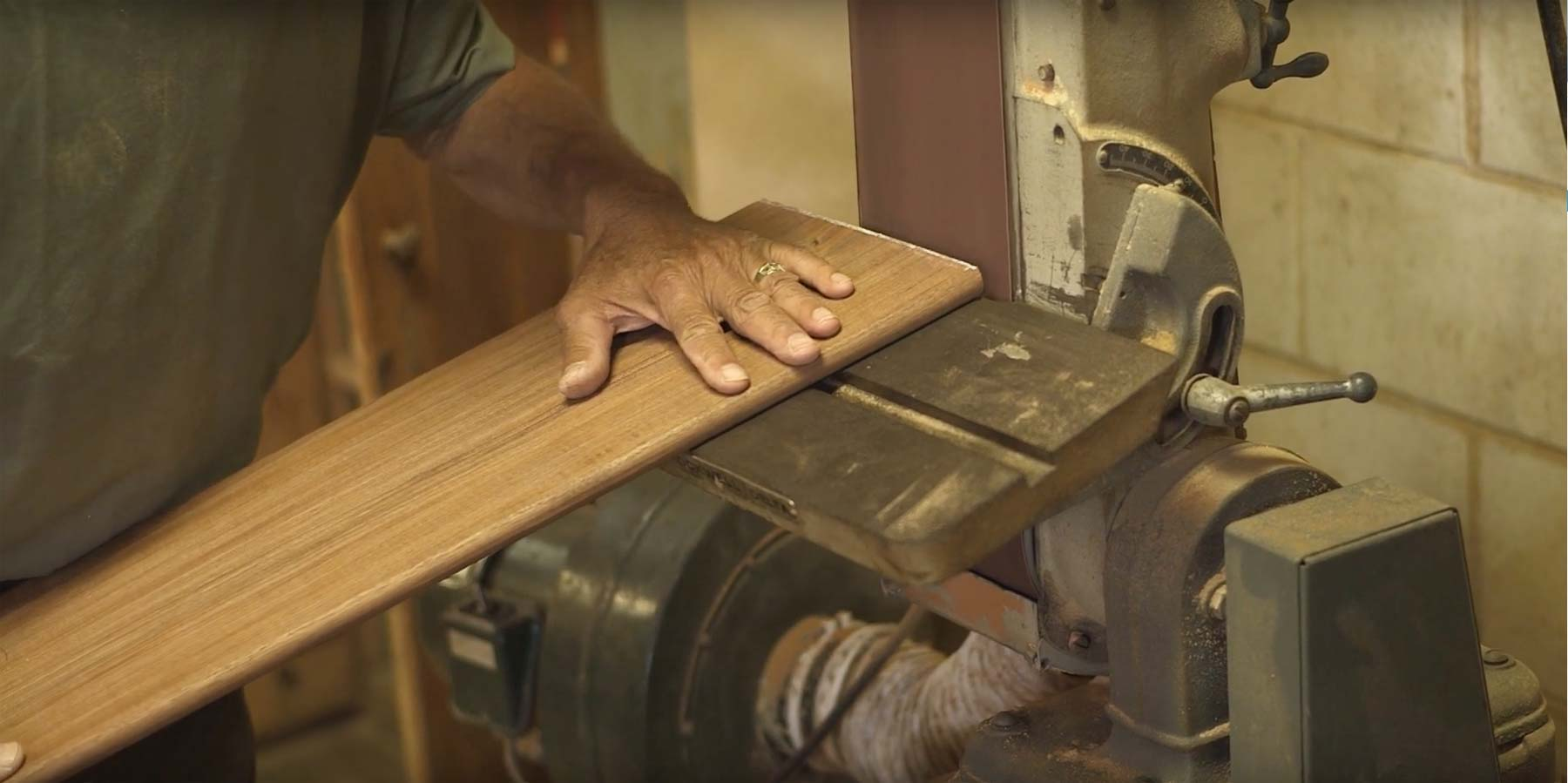 man's hands working through putting wood under a saw