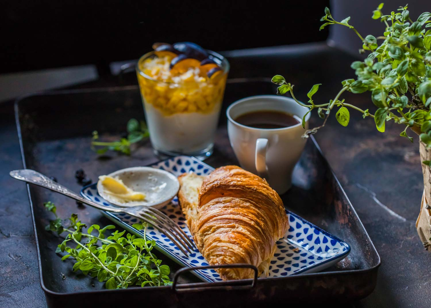 a fresh croissant and coffee on tray