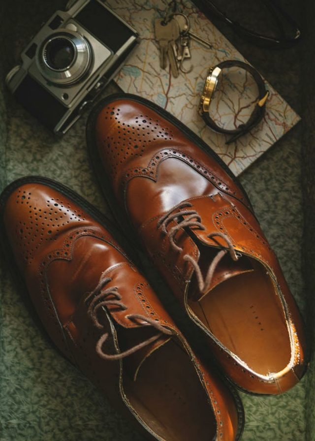 men's dress shoes next to a watch, camera and map