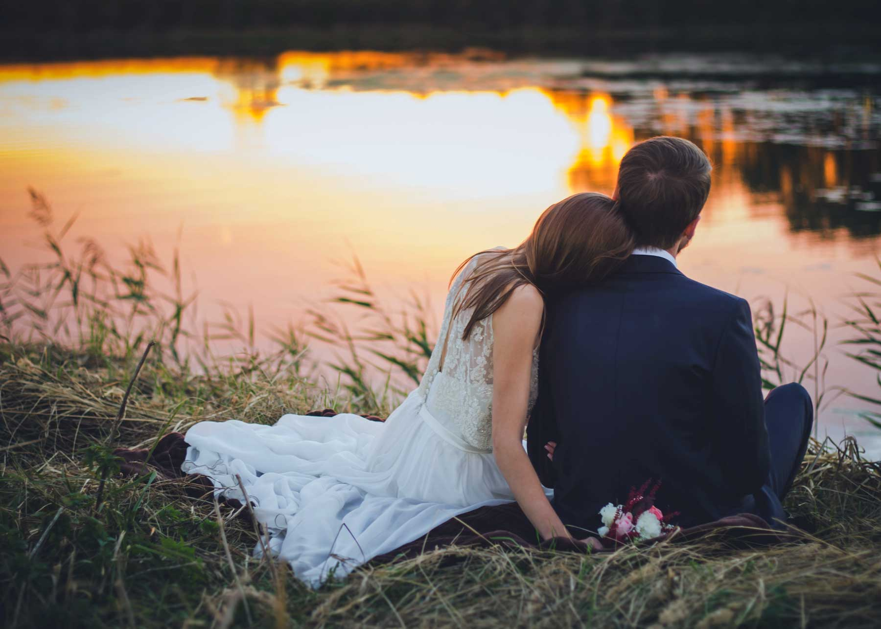 bride and groom lean on each other sitting near water's edge during sunset