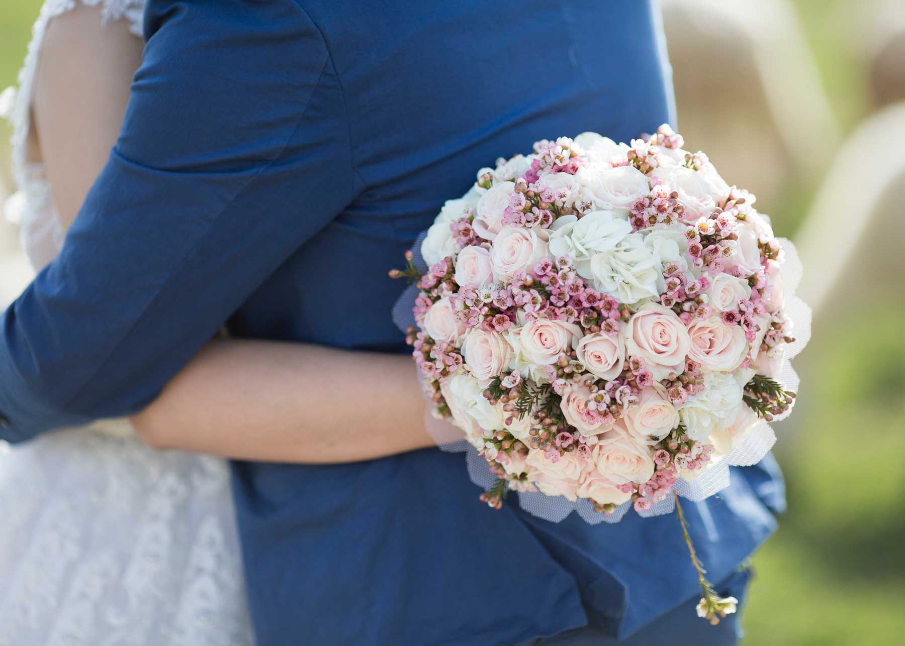 bride and groom embrace for hug while woman holds onto her full round flower bouquet