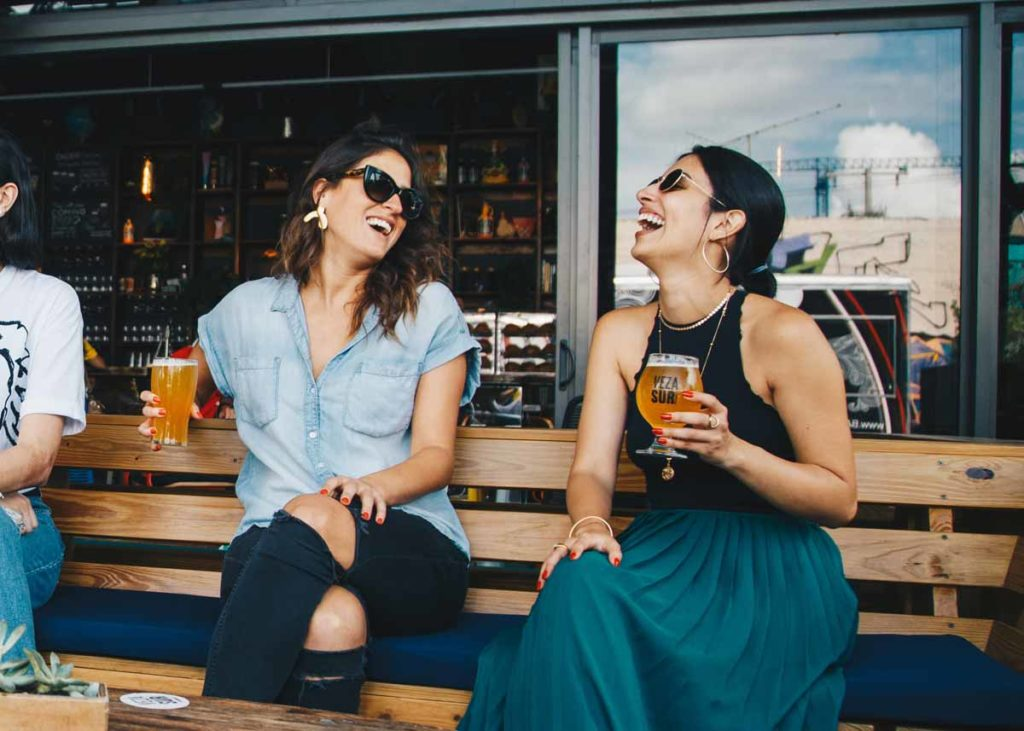 Two women happily enjoying their craft beer on a beautiful summer day in Beaufort NC