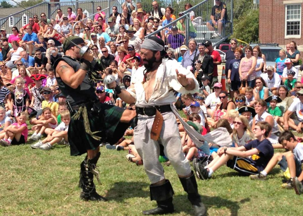 Crowds watch two pirates perform a sword-fighting demonstration at the Beaufort Pirate Invasion