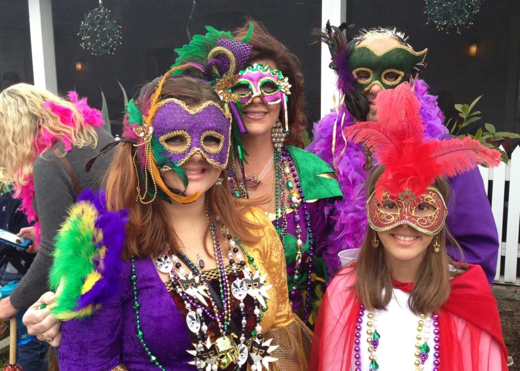Several people dressed in Mardi Gras costume and jewelry