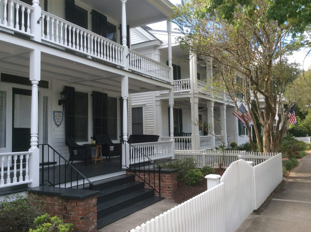 Front exterior of historic buildings with a white fence