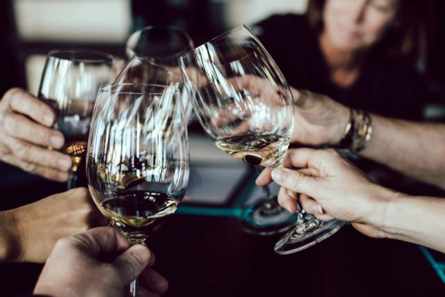 a group of friends clinking their wine glasses in celebration