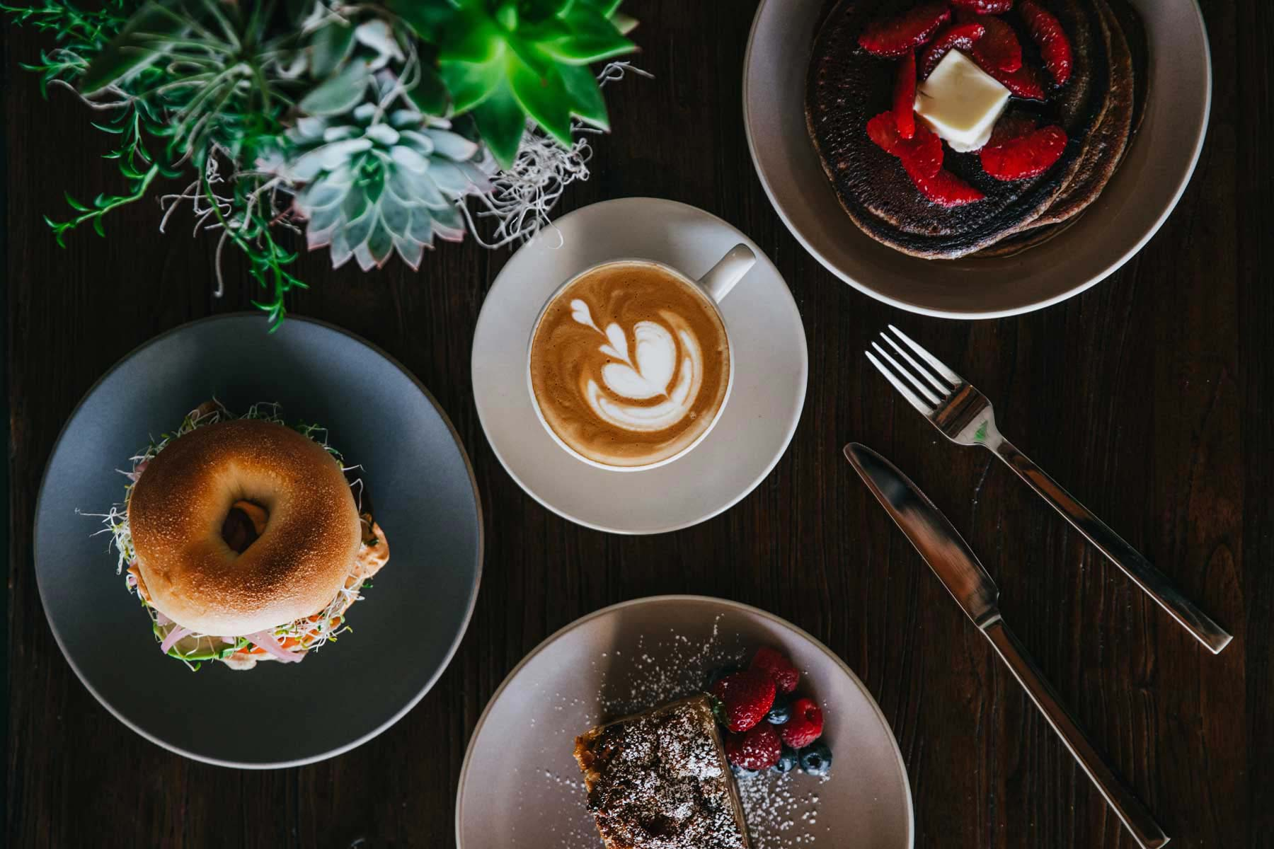 cappuccino, breakfast bagel, buttermilk pancakes topped with berries for brunch
