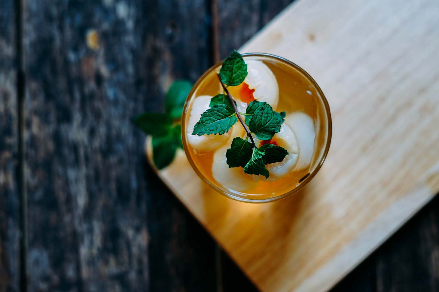 a cocktail on a wooden cutting board garnished with fresh mint leaves