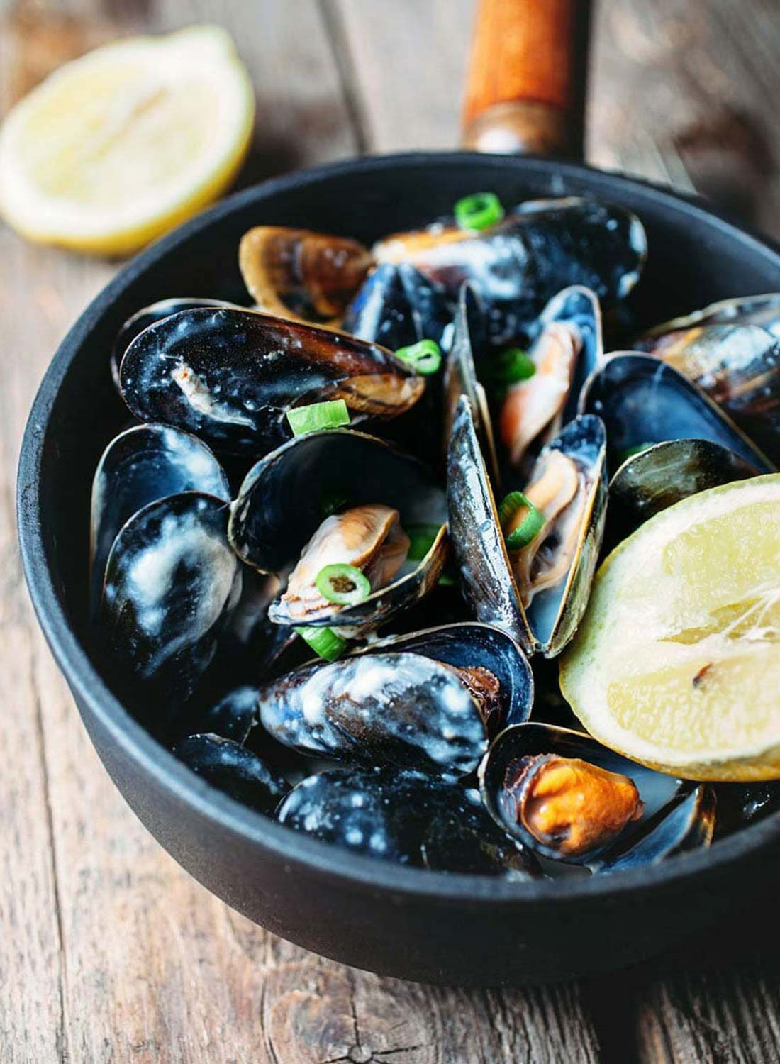 Freshly cooked mussels garnished with lemon in a pot