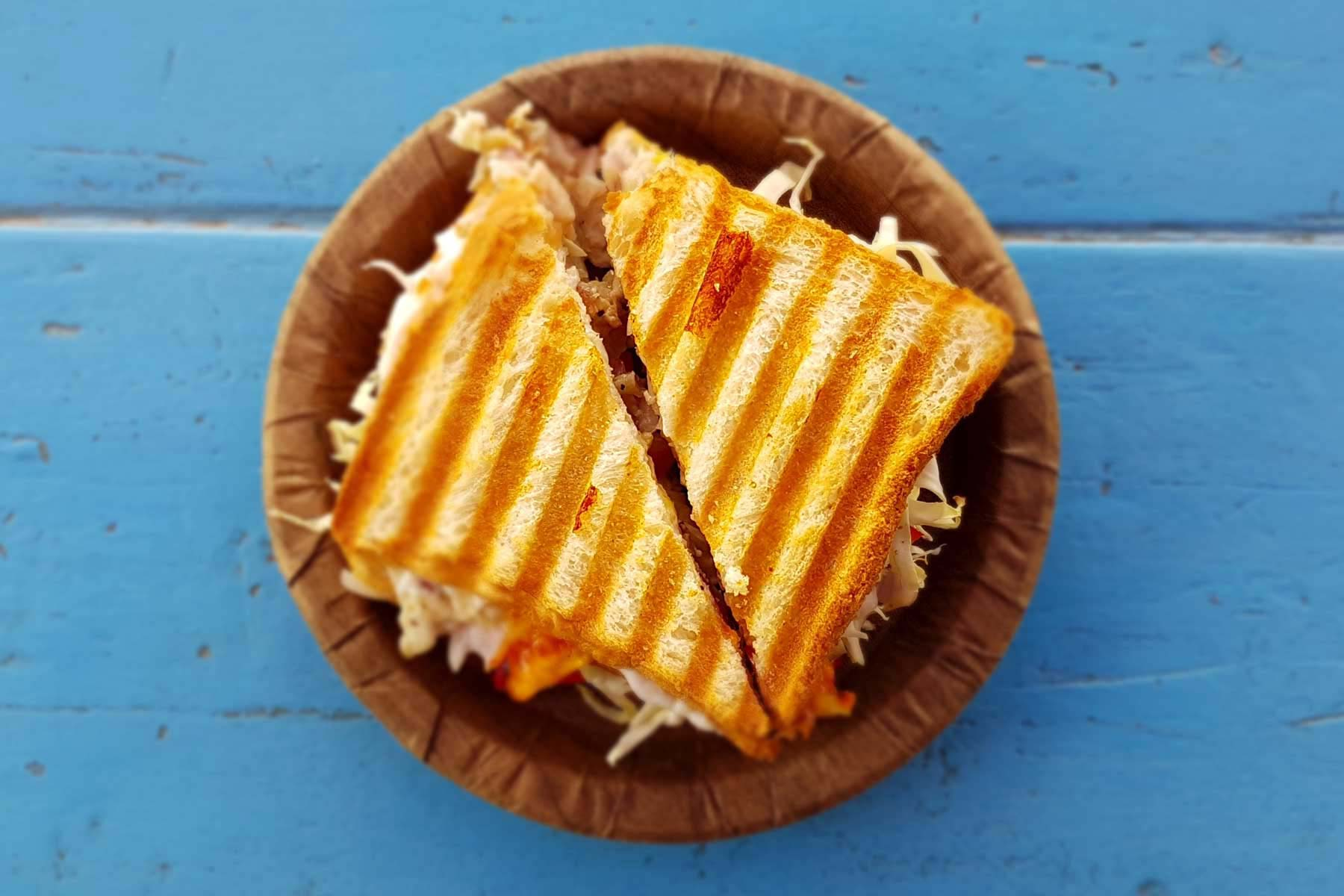 A toasted sandwich with grill marks on a brown plate sitting on a light blue painted wood table