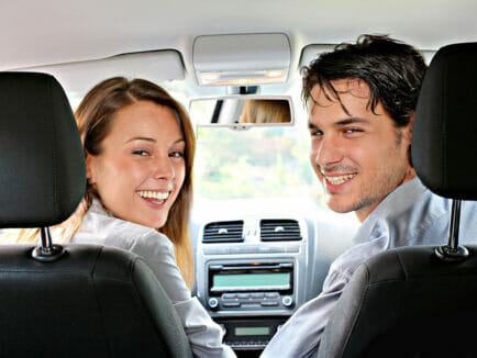 woman and man sit in front seats of vehical and turn to the back to smile for photo