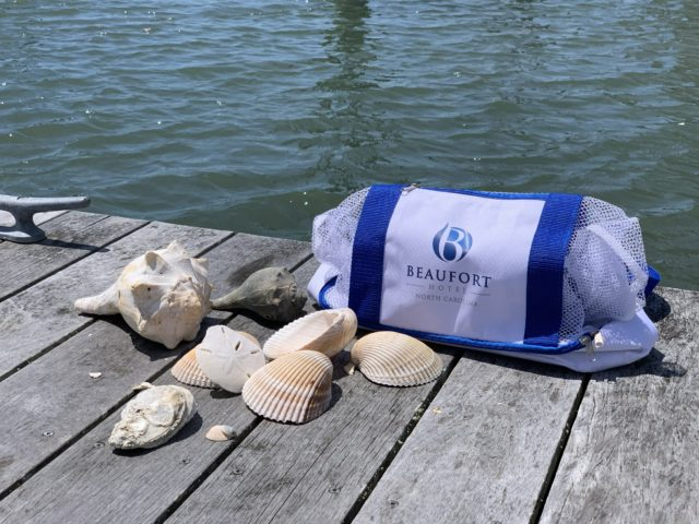 mesh travel bag from Beaufort Hotel, NC on the dock next to sea shells