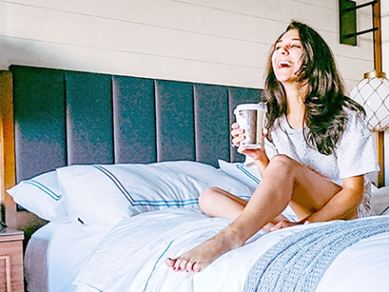 Person on bed with holding coffee smiling