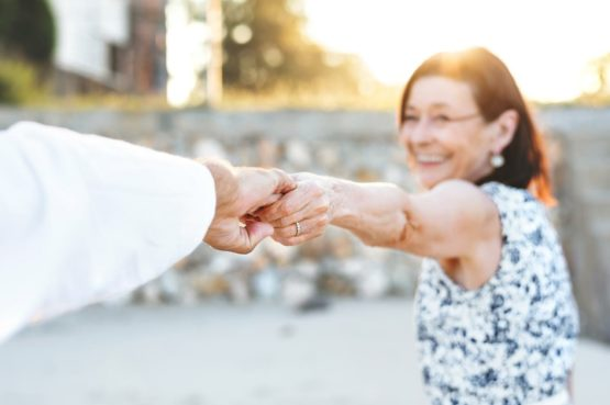 elderly couple happily holding hands while dancing in the summer time