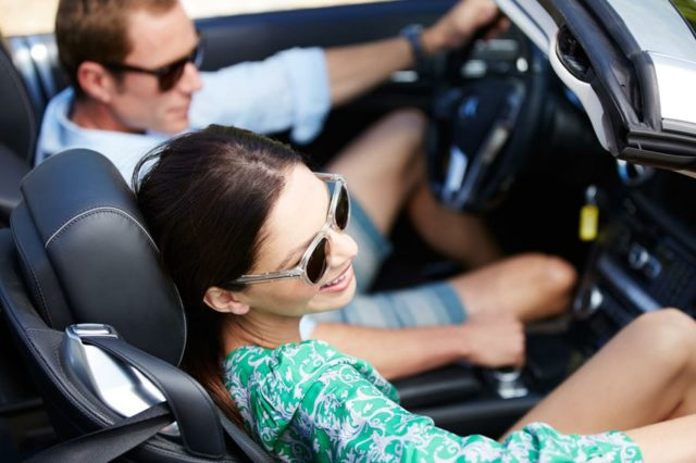 a man and woman happily driving in convertible with sunglasses on in the summer time