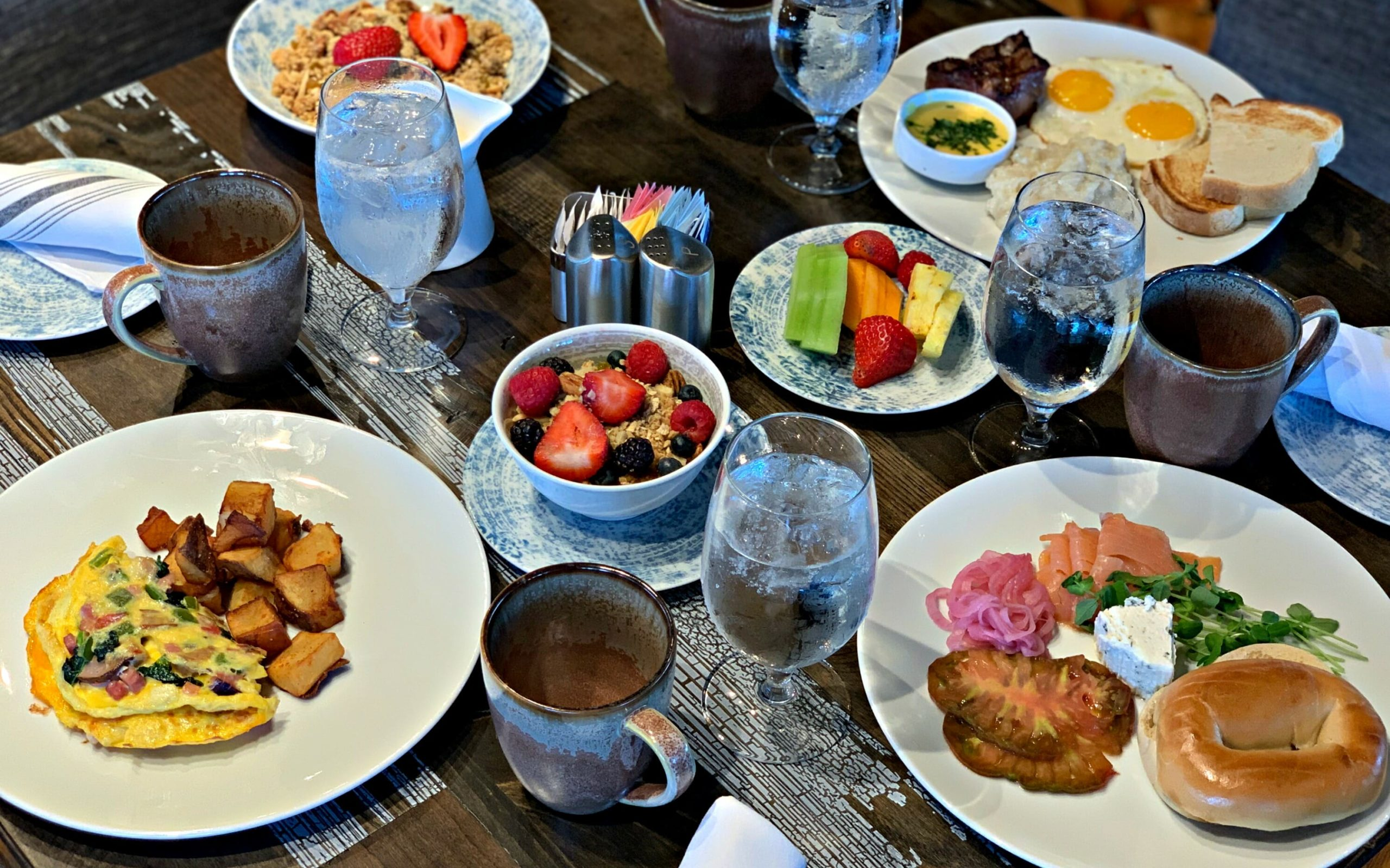 an array of breakfast dishes on wooden table