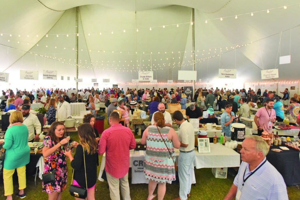 people gathered under white tent for food and wine