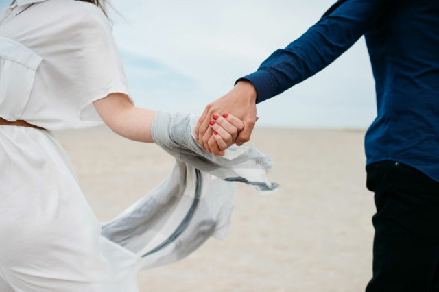 couple holds hands while on the beach