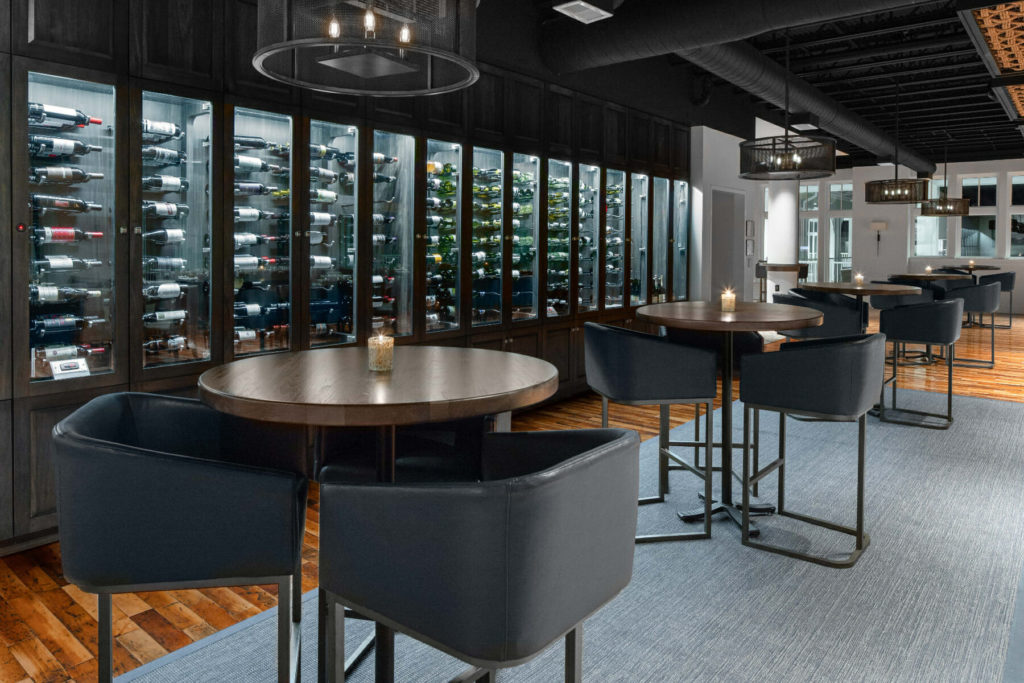 five tall tables with chairs in front of wine rack