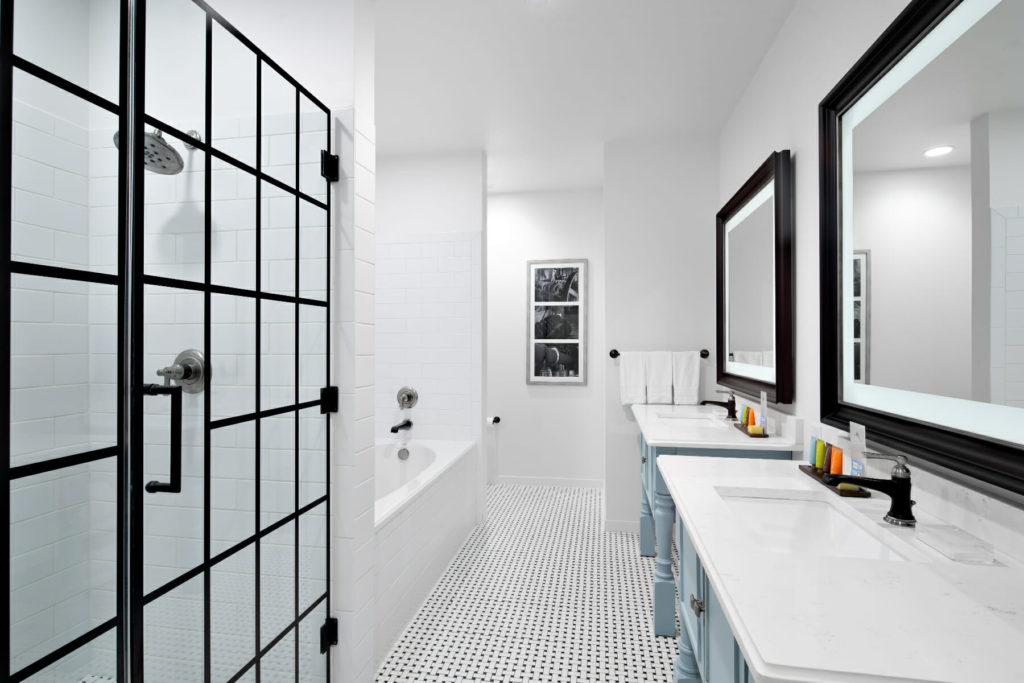 bathroom with double vanity stand up shower and bath tub
