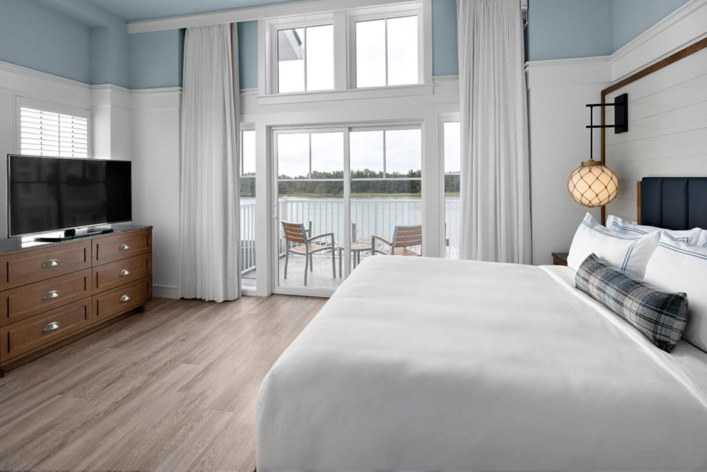 bed in front of wooden dresser with tv
