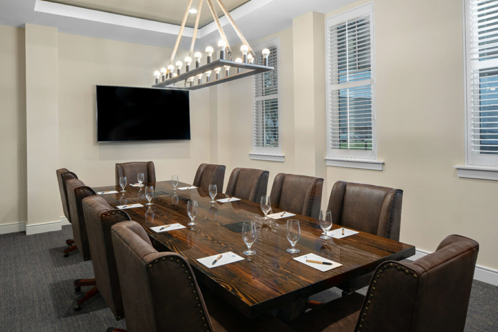 meeting room with wooden table and brown leather chairs