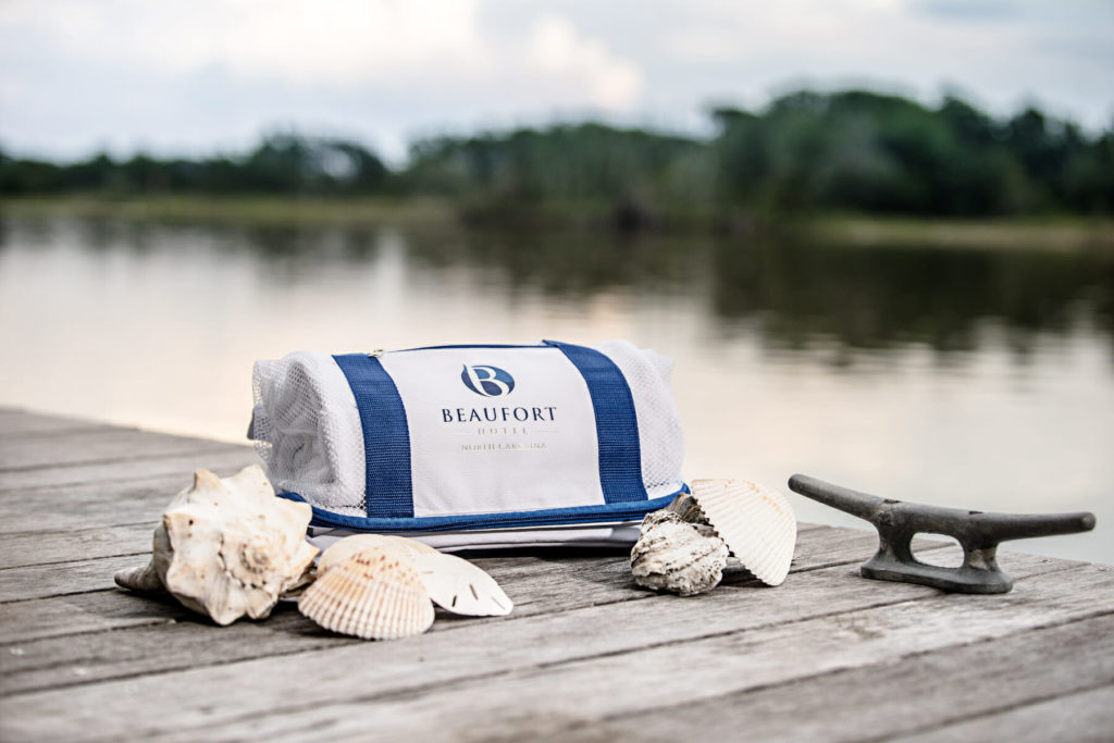 mesh shelling bag sitting on wooden dock with shells
