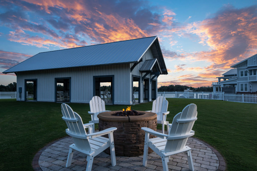 fire pit surrounded by four white chairs at sunset