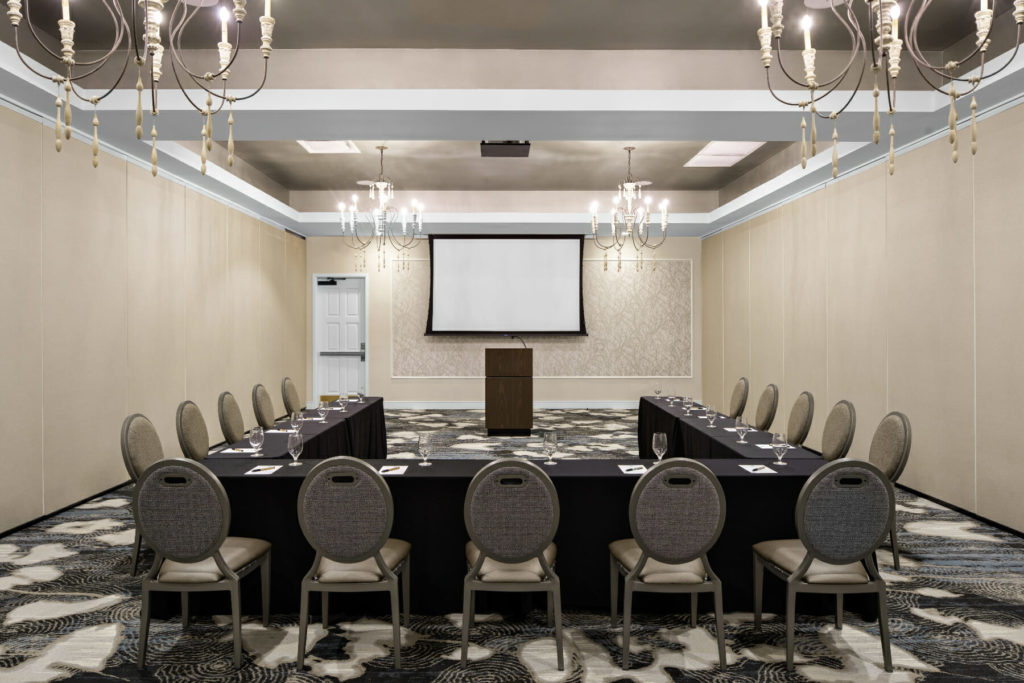 large meeting room in u-shaped formation with screen in the background