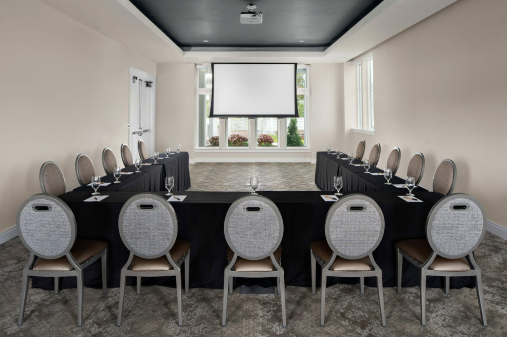 meeting room in u-shaped formation with screen in the background
