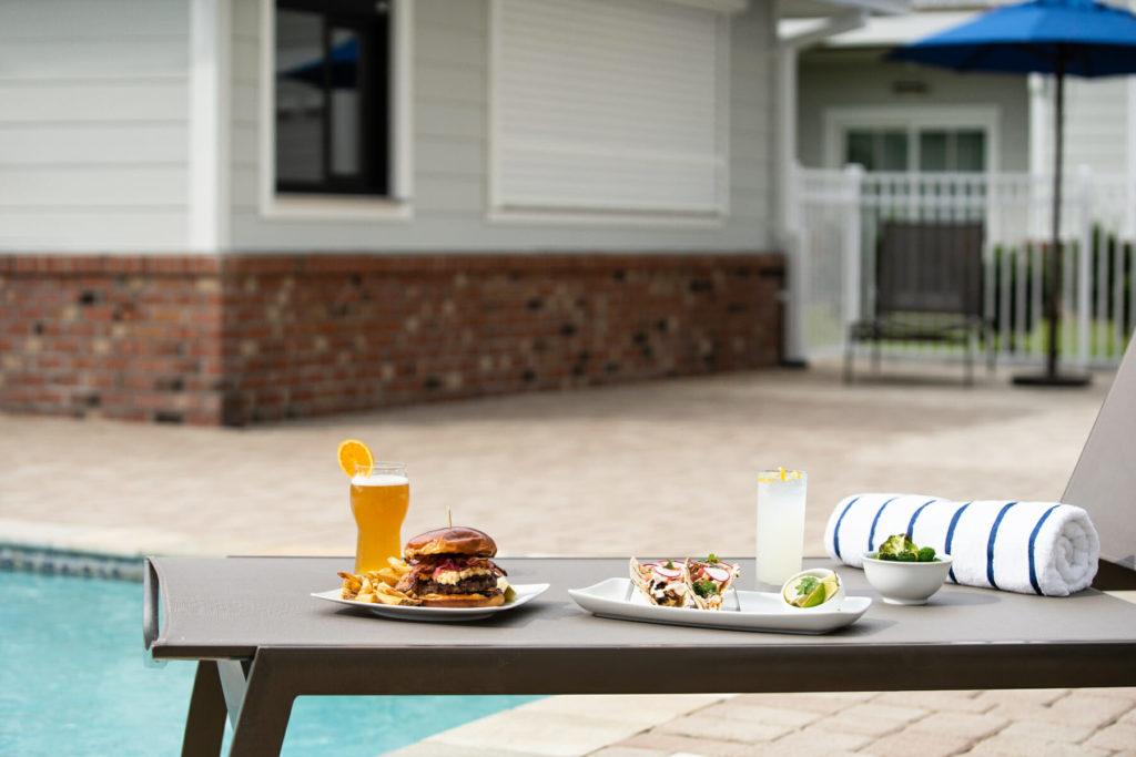 drinks, food, and towel on chair beside pool