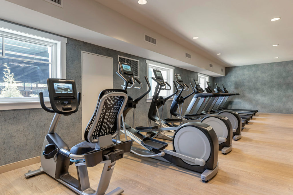 fitness equipment lined up in front of wall with windows