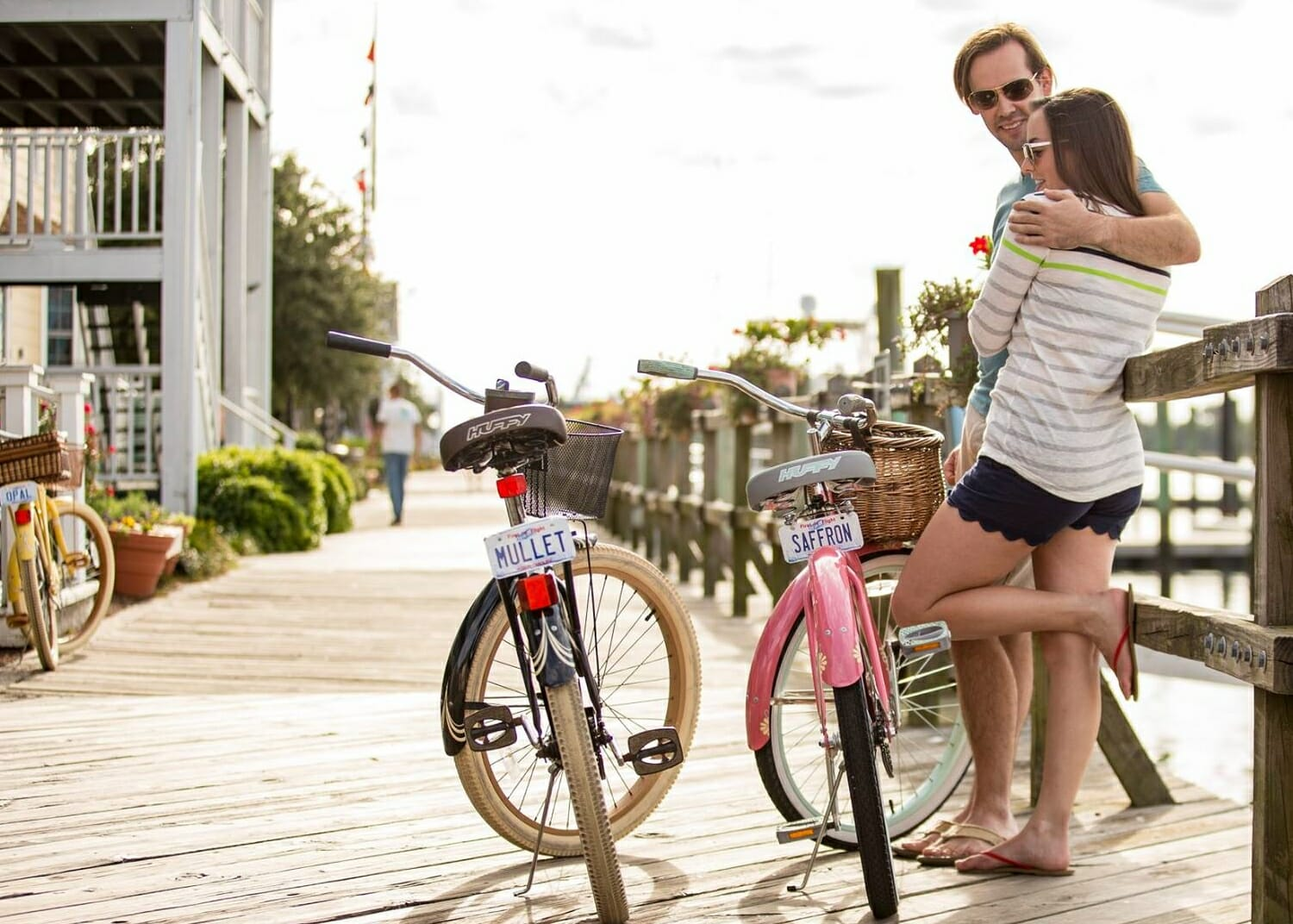 man and woman standing on boardwalk beside black and pink bikes