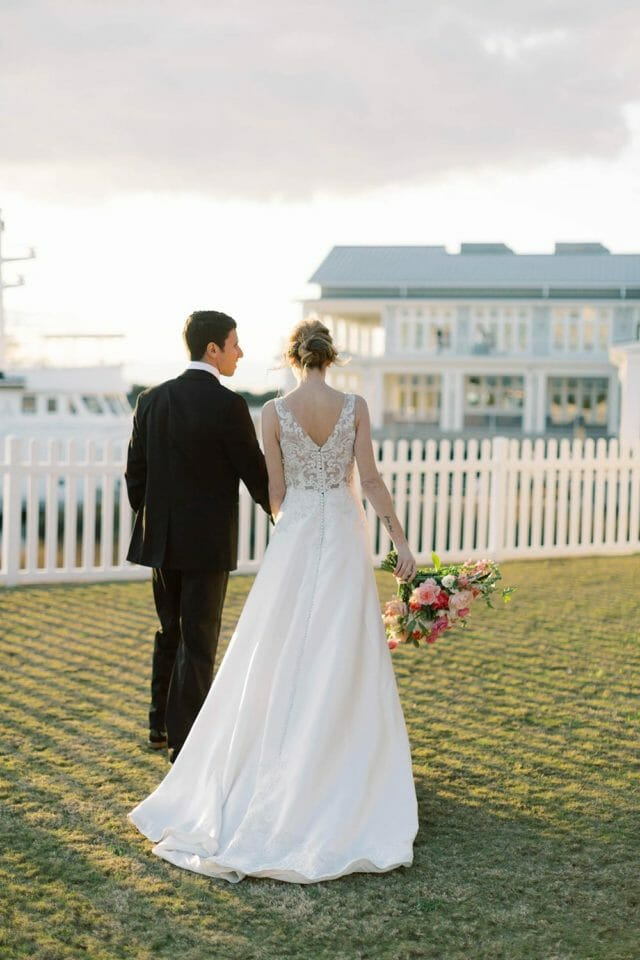 bride and groom walking the grounds of Beaufort Hotel, NC wedding venue