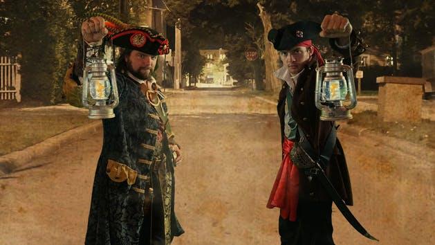 Two pirates holding up lanterns