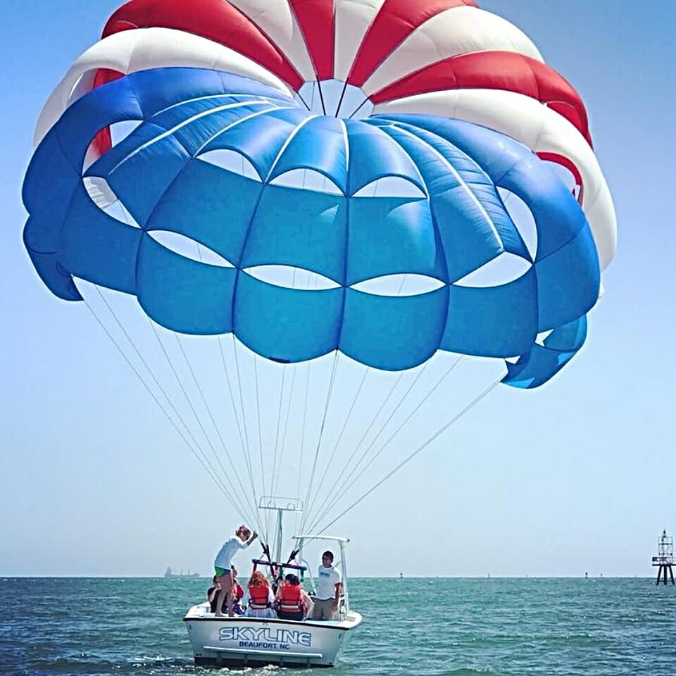 boat on lake with people preparing to parasail