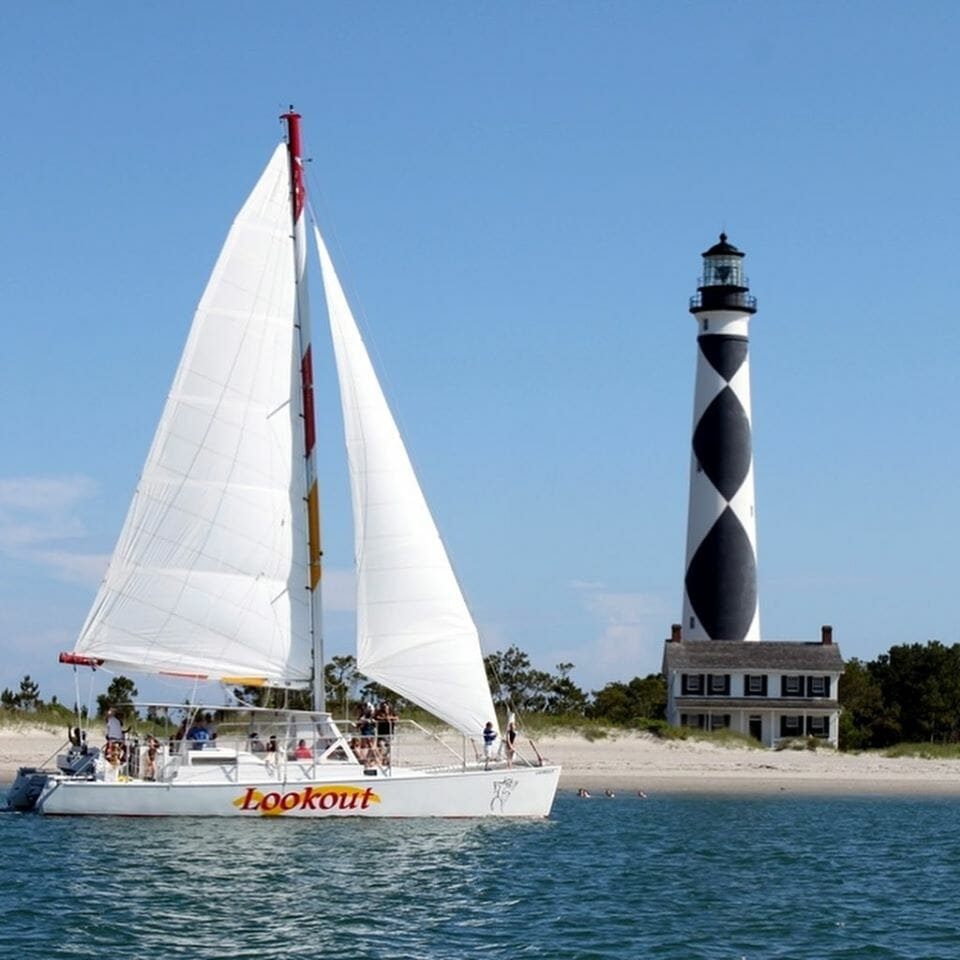 sail boat in the water with lighthouse in the background