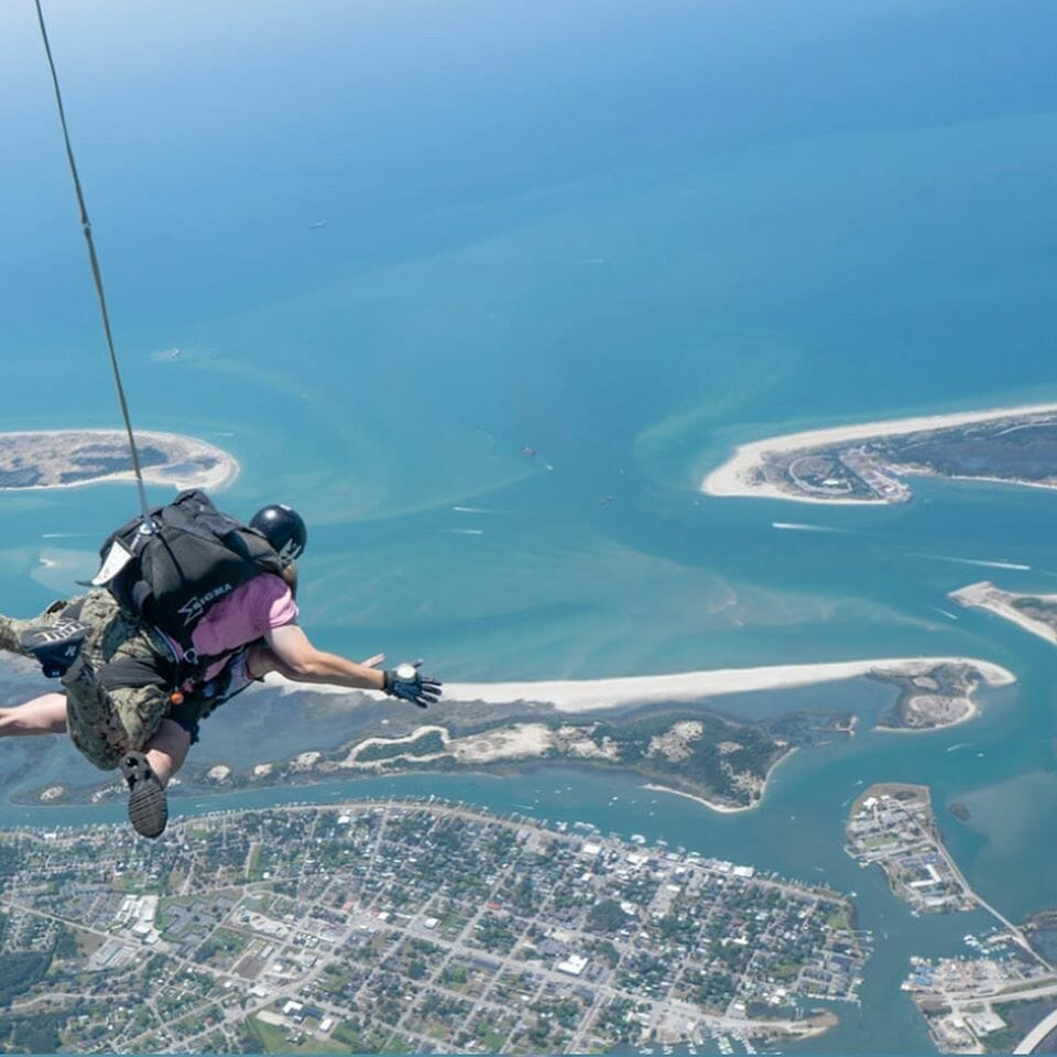 pair skydiving over city with parachute string deployed