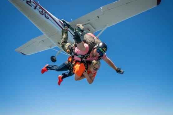 person skydiving out of plane strapped to professional guide