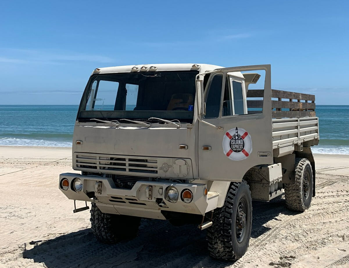 Large beige truck parked on beach