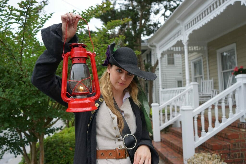 Person in old time clothing holding lamp