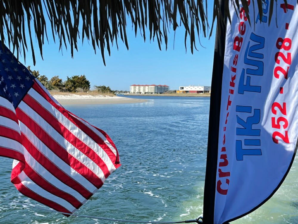 View of water and buildings through flags on tiki boat