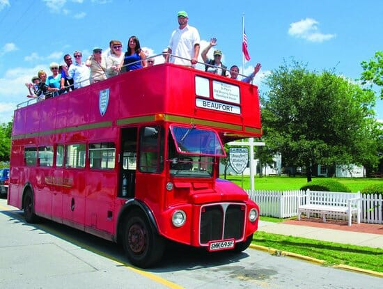 People on top of a red double decker bus