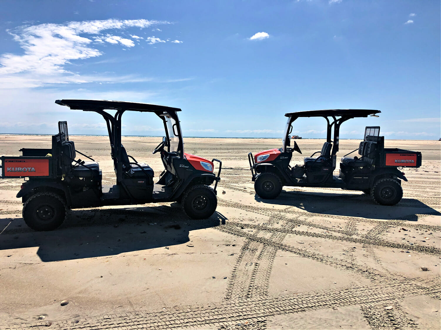 Two multiple seat all terrain vehicles on a beach
